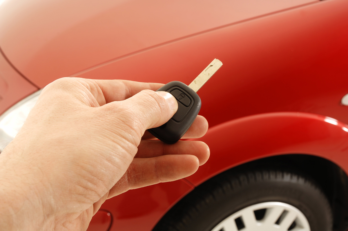 Person holds a car key in front of a red 2005 Citroen C3.