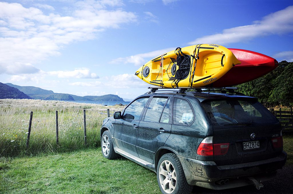 car parked on the grass with kayaks on top