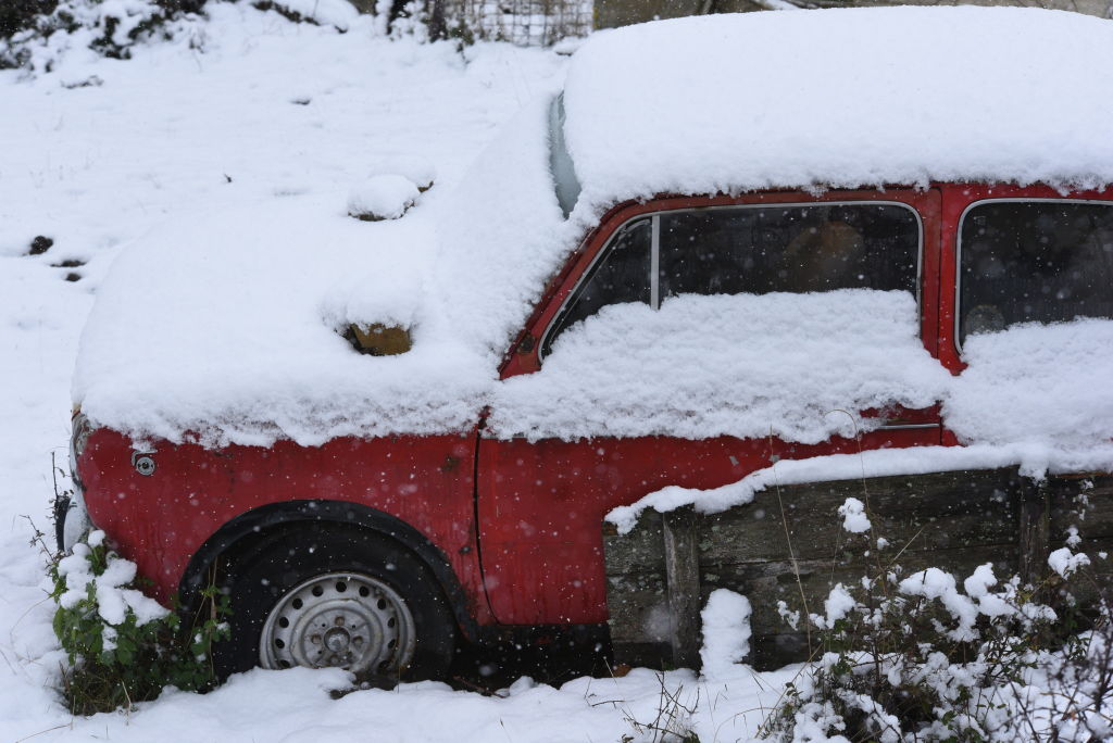 a red car piled under a lot of snow