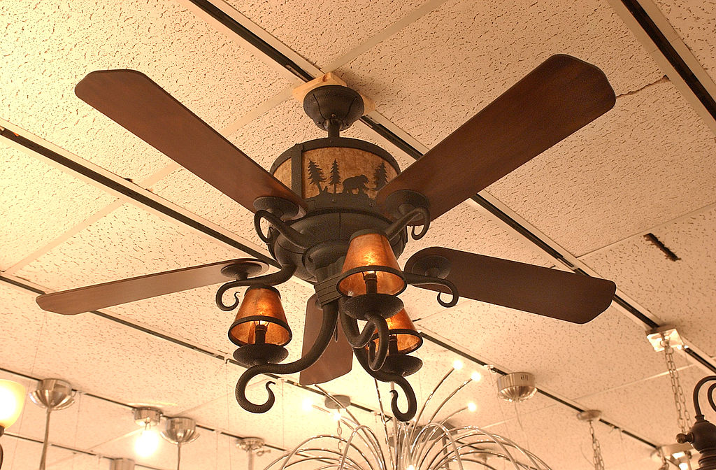a ceiling fan with a bear and forest design