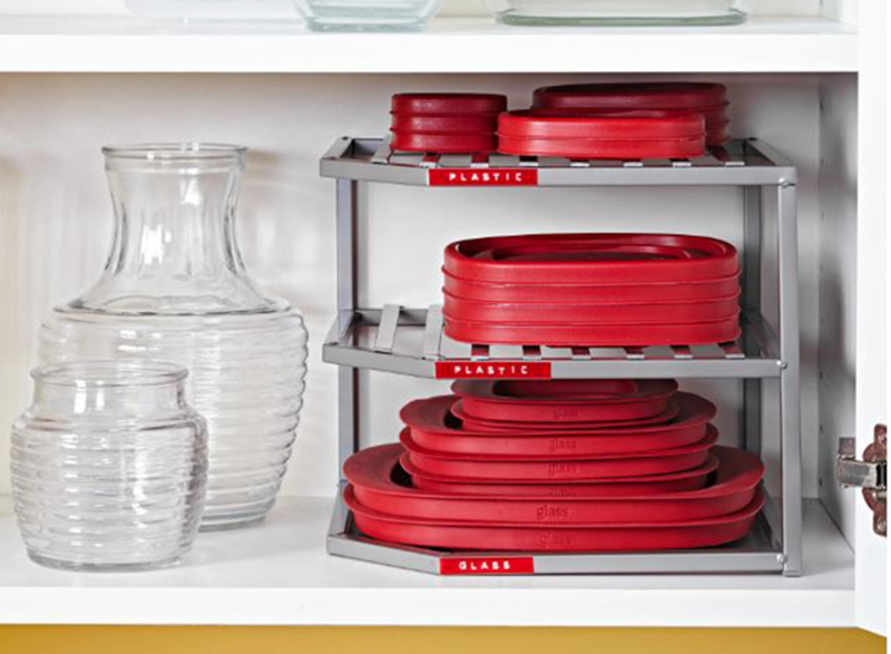A plastic corner organizer stores tupperware lids on a shelf.