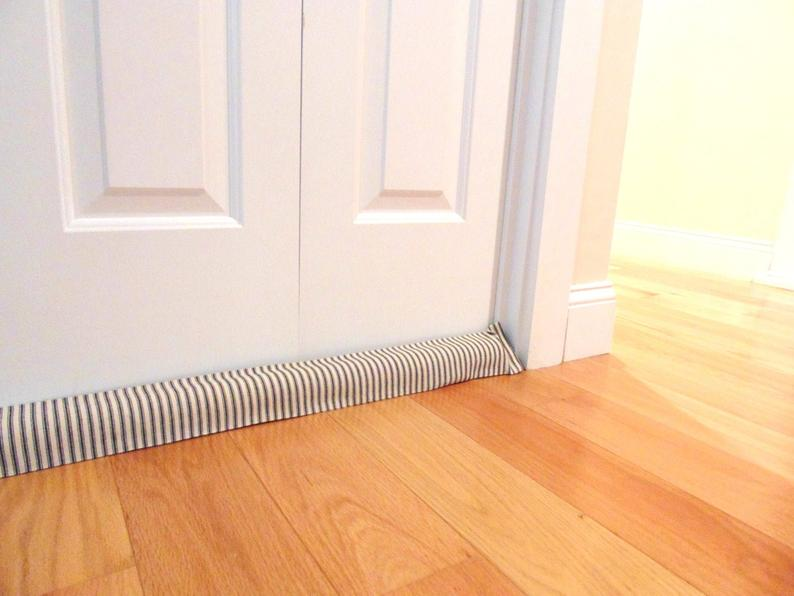 a striped door draft stopper under a door