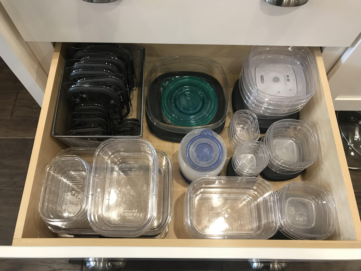 Drawer is filled with stacked, organized tupperware.
