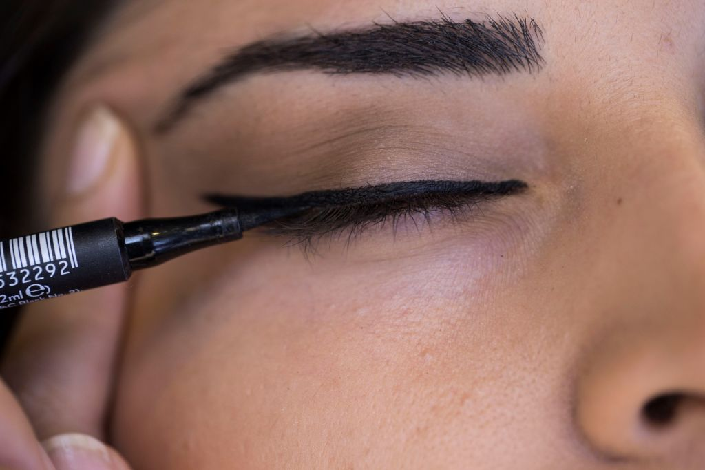 a woman applying black eyeliner