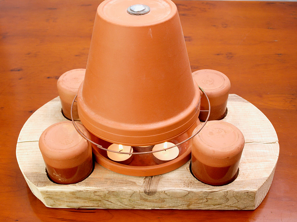 a flower pot covering tea lights on a wooden holder
