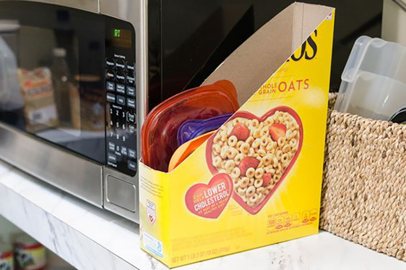 A reused cereal box holds tupperware lids.