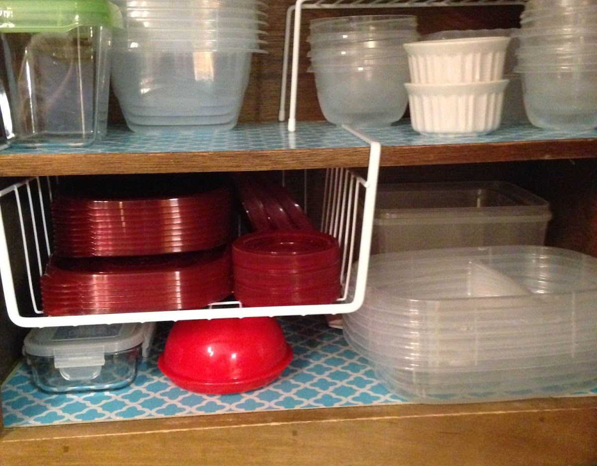 Tupperware lids are in an wire under-shelf basket.