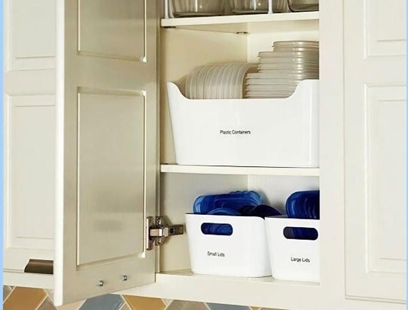 Labeled bins hold tupperware in a kitchen cupboard.