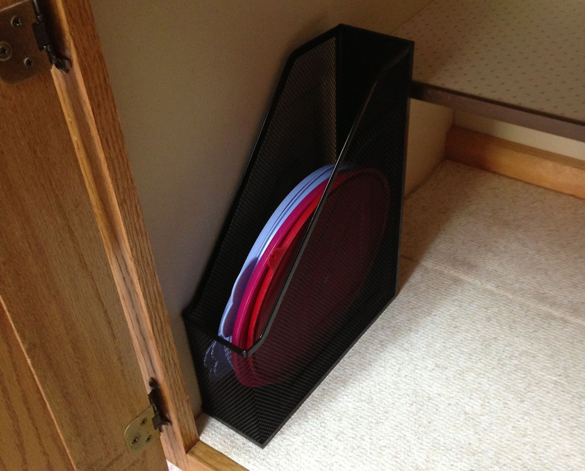 A magazine rack holds tupperware lids in a kitchen cabinet.