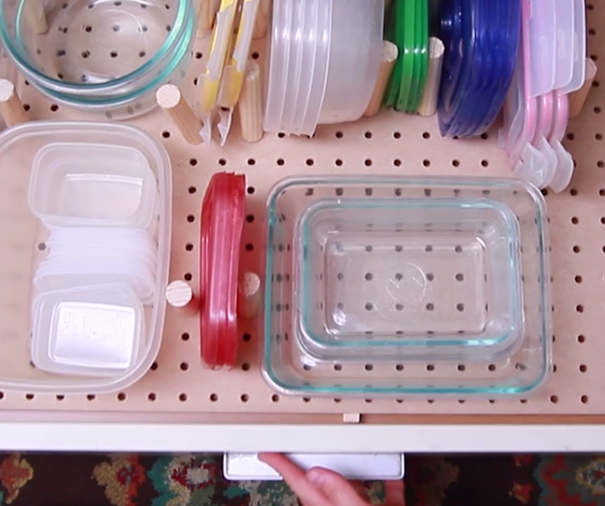 Tupperware is organized with a pegboard inside of a drawer.