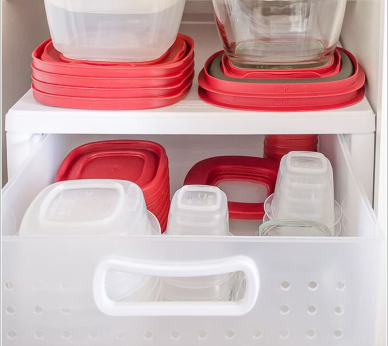 Plastic drawers hold tupperware.
