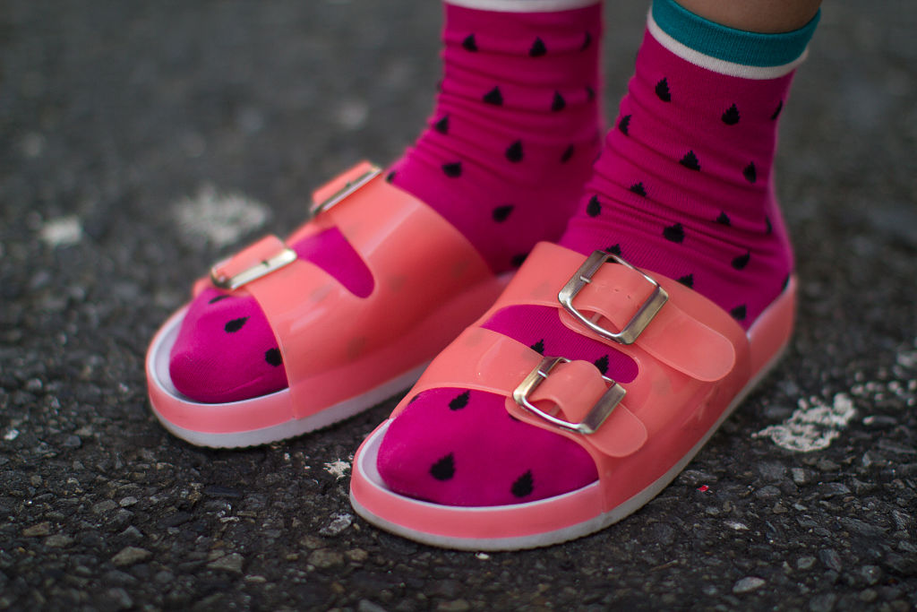 a person wearing pink watermelon socks and plastic pink sandals