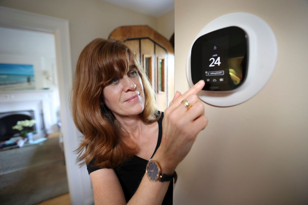 a woman using a thermostat attached to the wall