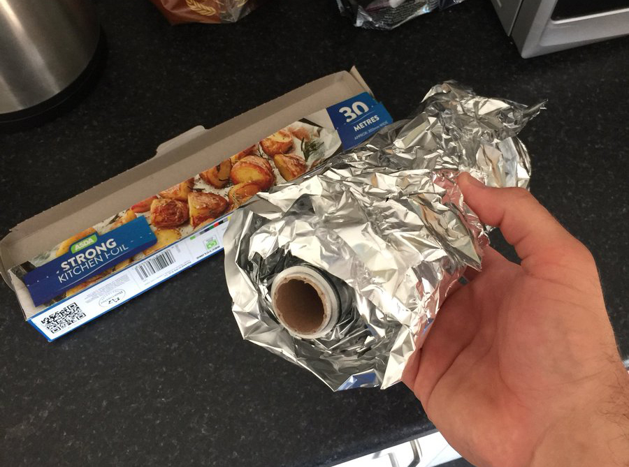 A person lifts the tin foil roll out of its box.
