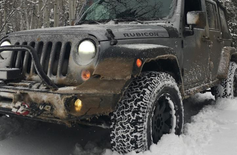 A jeep has wax on its headlights in the snow.