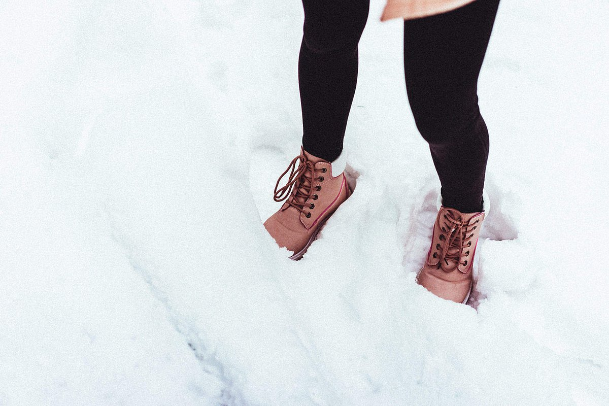 A woman wears pink shoes in the snow.
