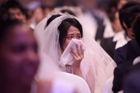 A bride cries in a crowd of people.