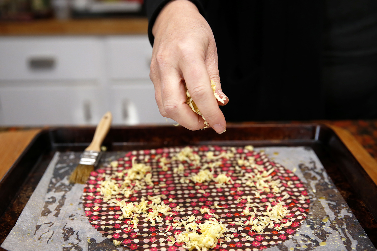 A person sprinkles beeswax pieces onto a cloth before briefly melting it in the oven.
