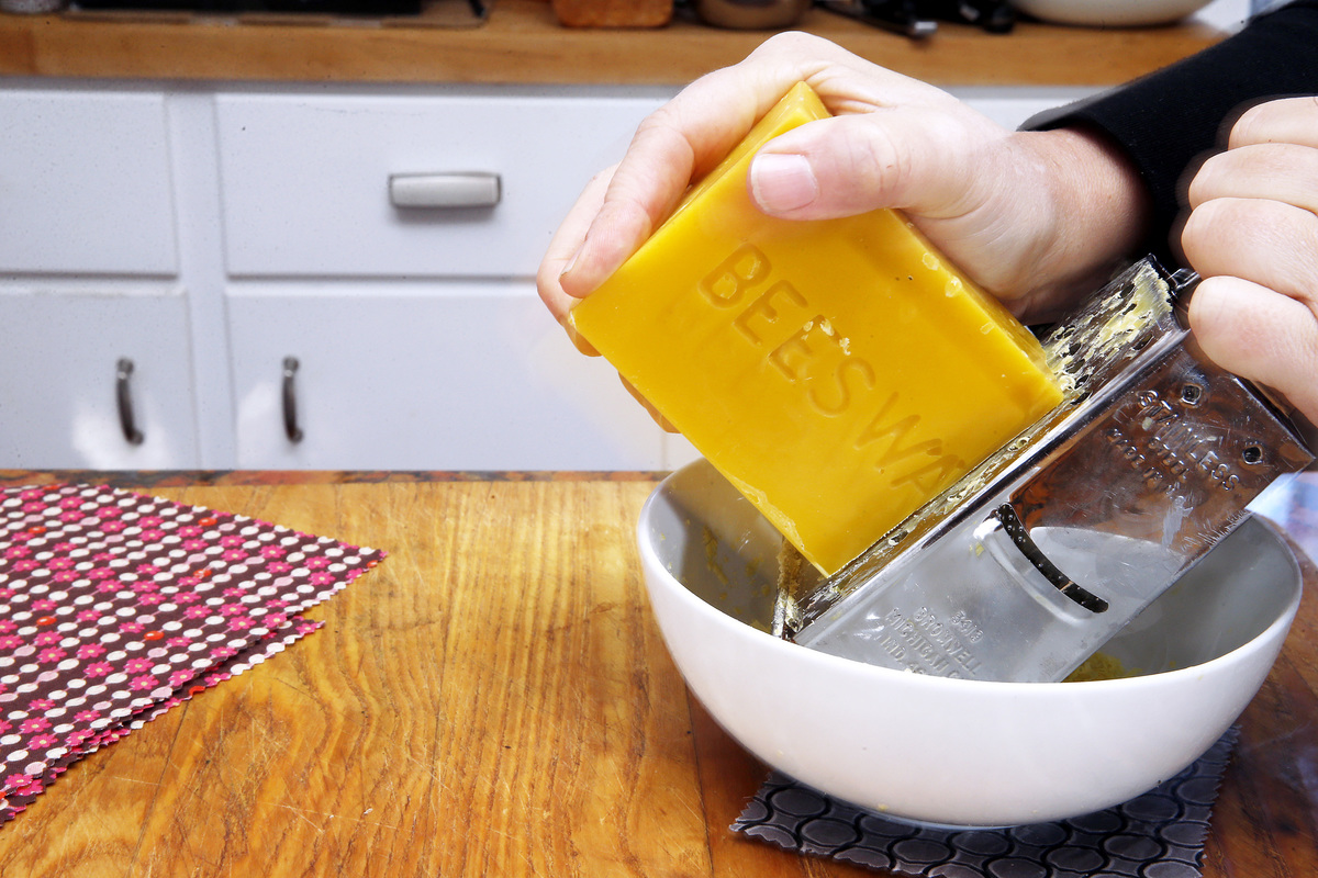 A man grates beeswax to make a sustainable alternative to plastic food wrap.