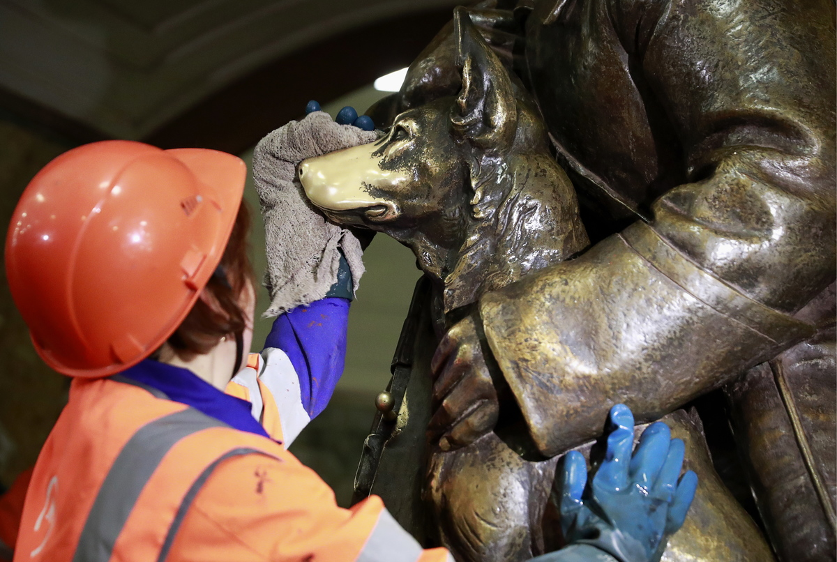 A maintenance worker washes a bronze statue of a dog.