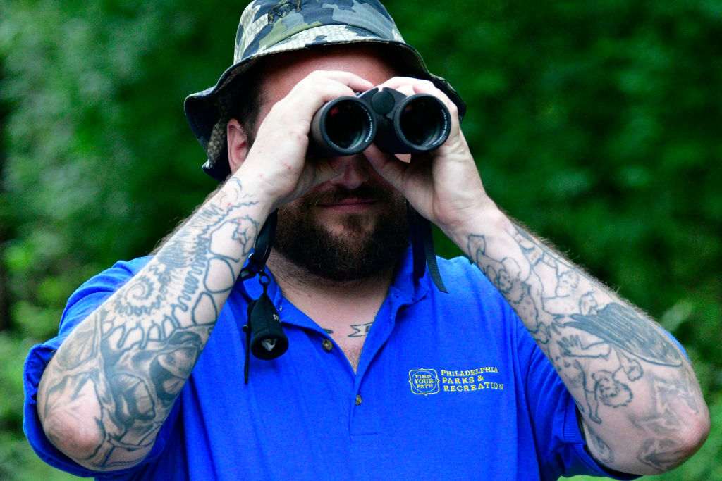 A man in the forest looks through binoculars.