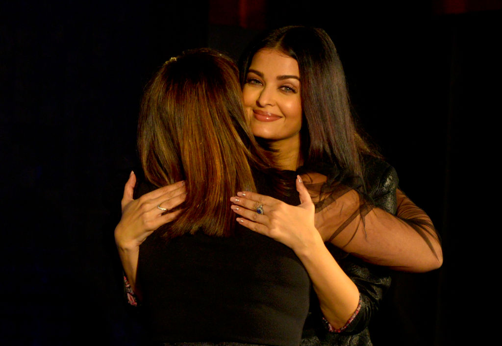 A woman smiles to the camera while giving a hug.