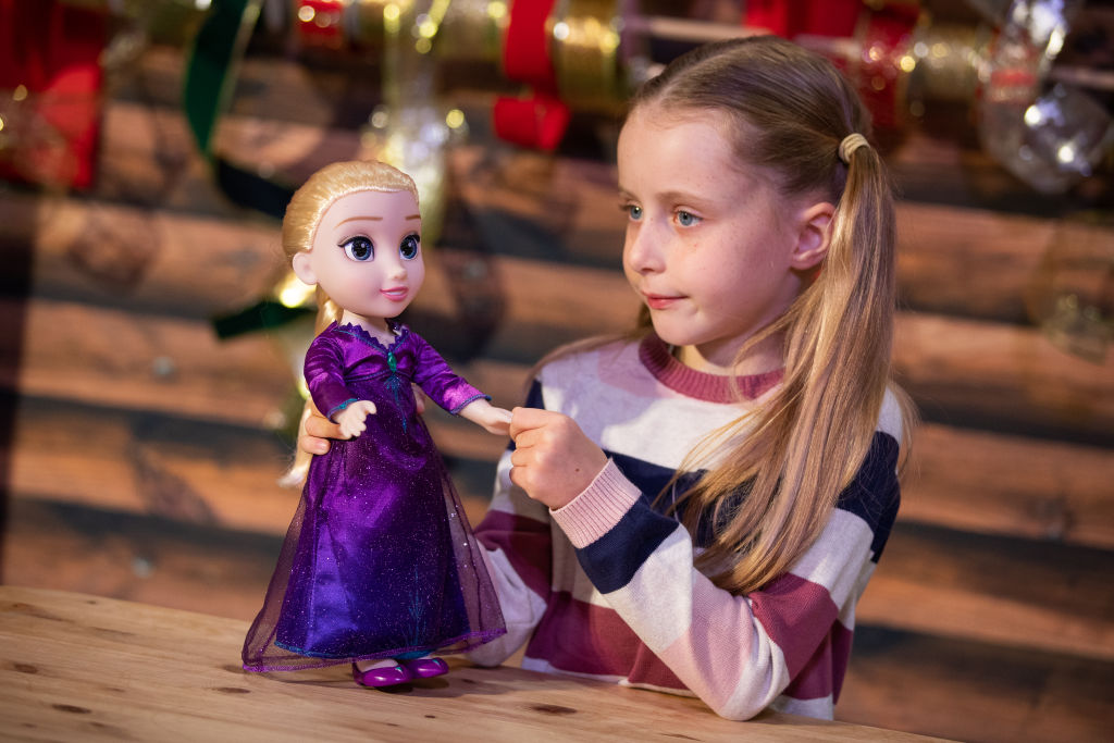 A girl holds her Elsa doll.