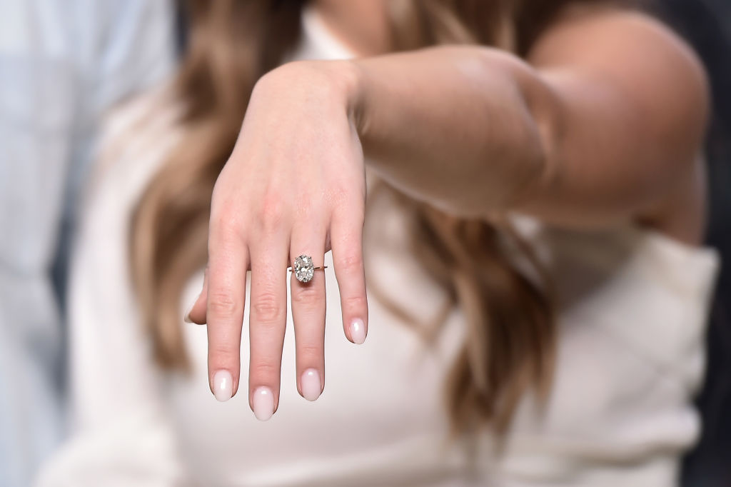 A woman holds out her hand to show her large, diamond engagement ring.
