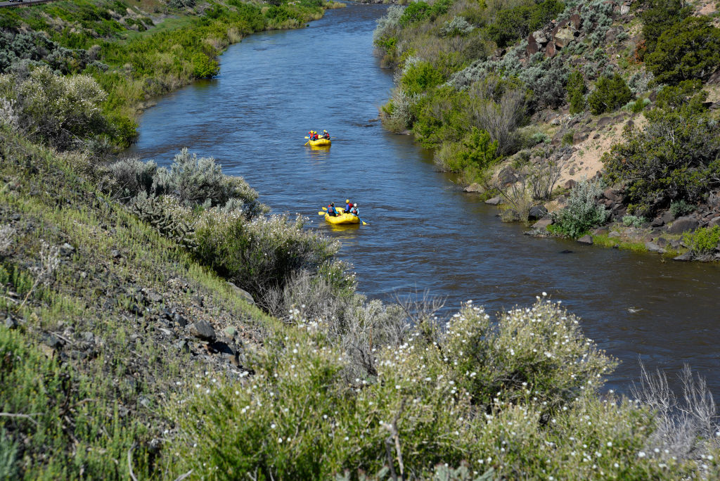 Two rafts carrying humans drift down a river.