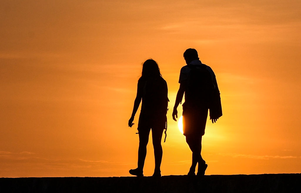 A couple is silhouetted while walking at sunset.