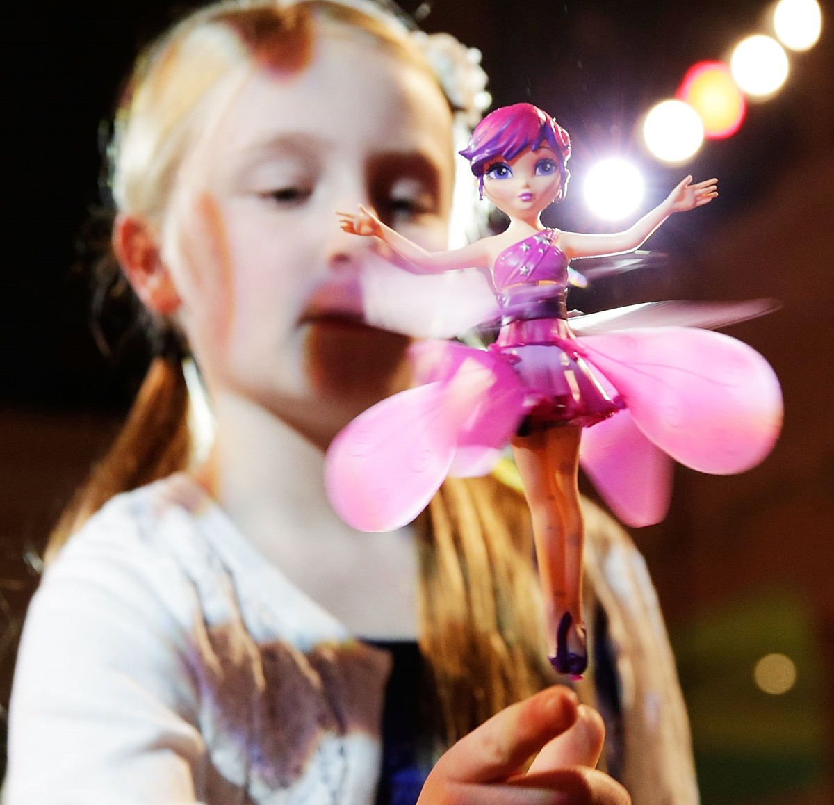 A girl places a finger underneath a flying fairy toy.