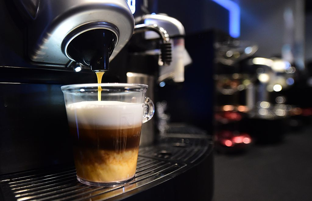 A coffee machine creates a caffeine beverage.