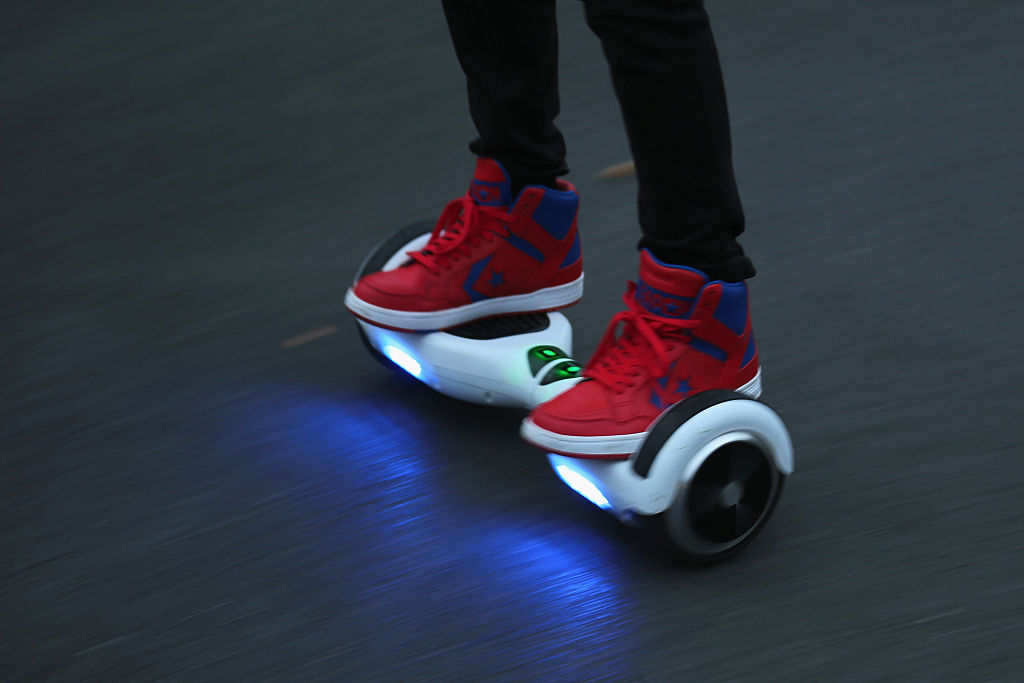 A boy rides a Hoverboard.