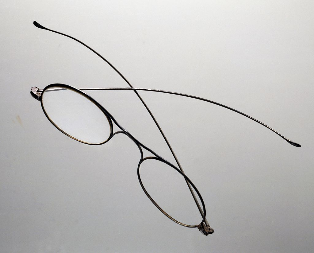 Eye glasses are photographed midair with a blank backdrop.