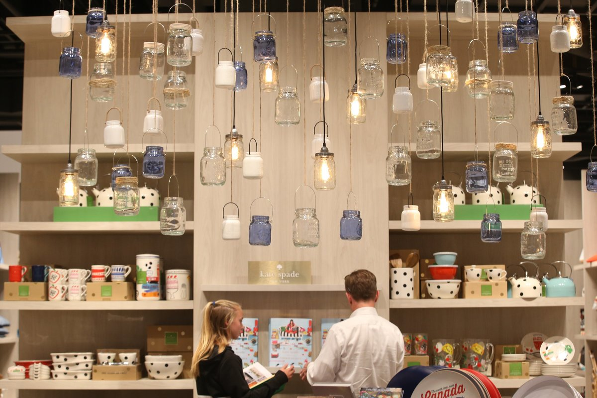 Home owners stand under a mason jar chandelier.