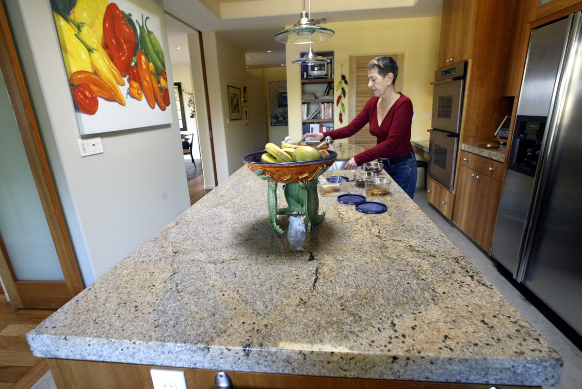 Myra Rosen works inside kitchen with a granite countertop at her home.