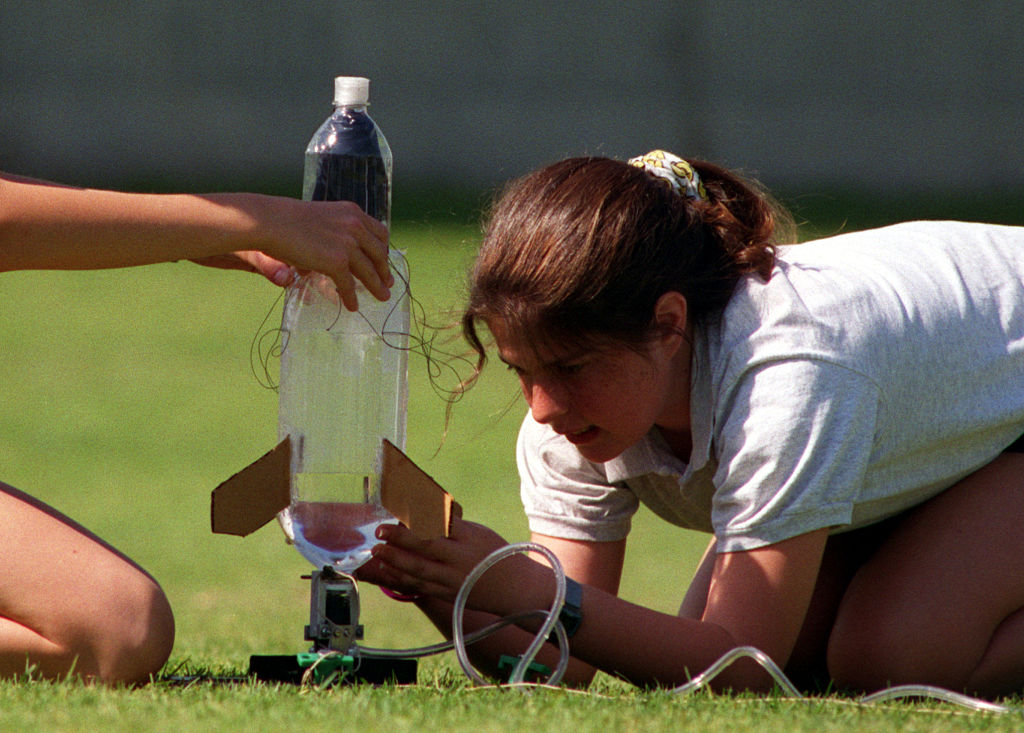 A young girl and her friend prepare to launch a bottle rocket.