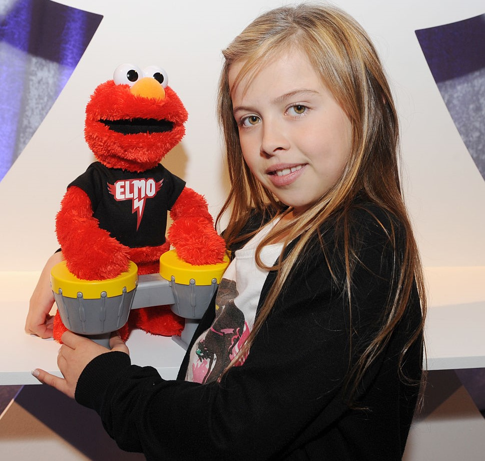 A young girl holds her Let's Rock Elmo.