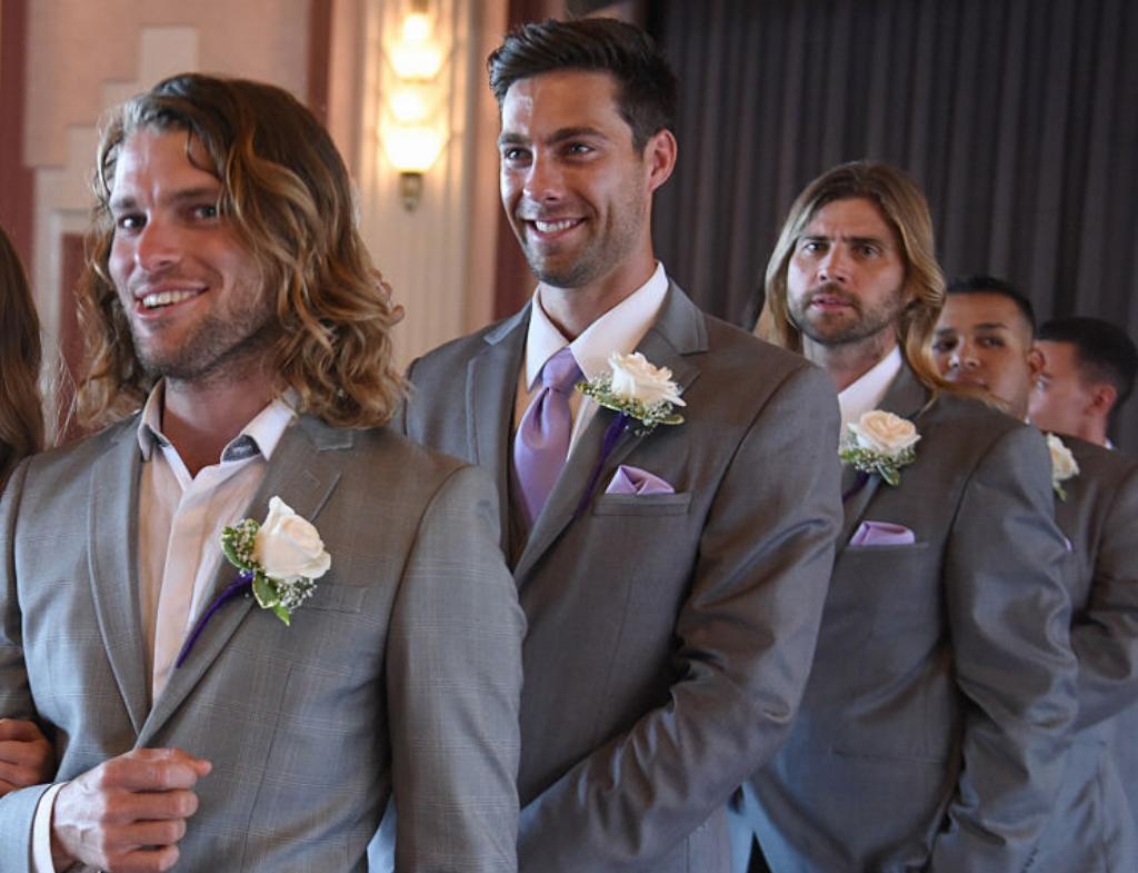 Groomsmen prepare to walk down the aisle.