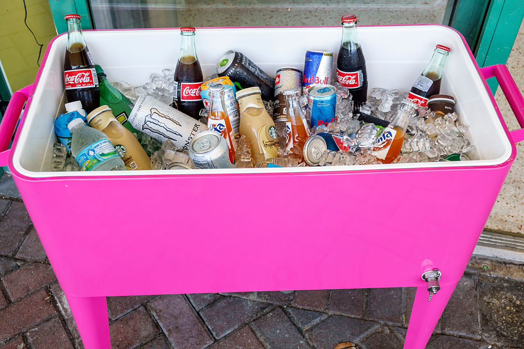 A hot pink cooler is full of various beverages and ice.