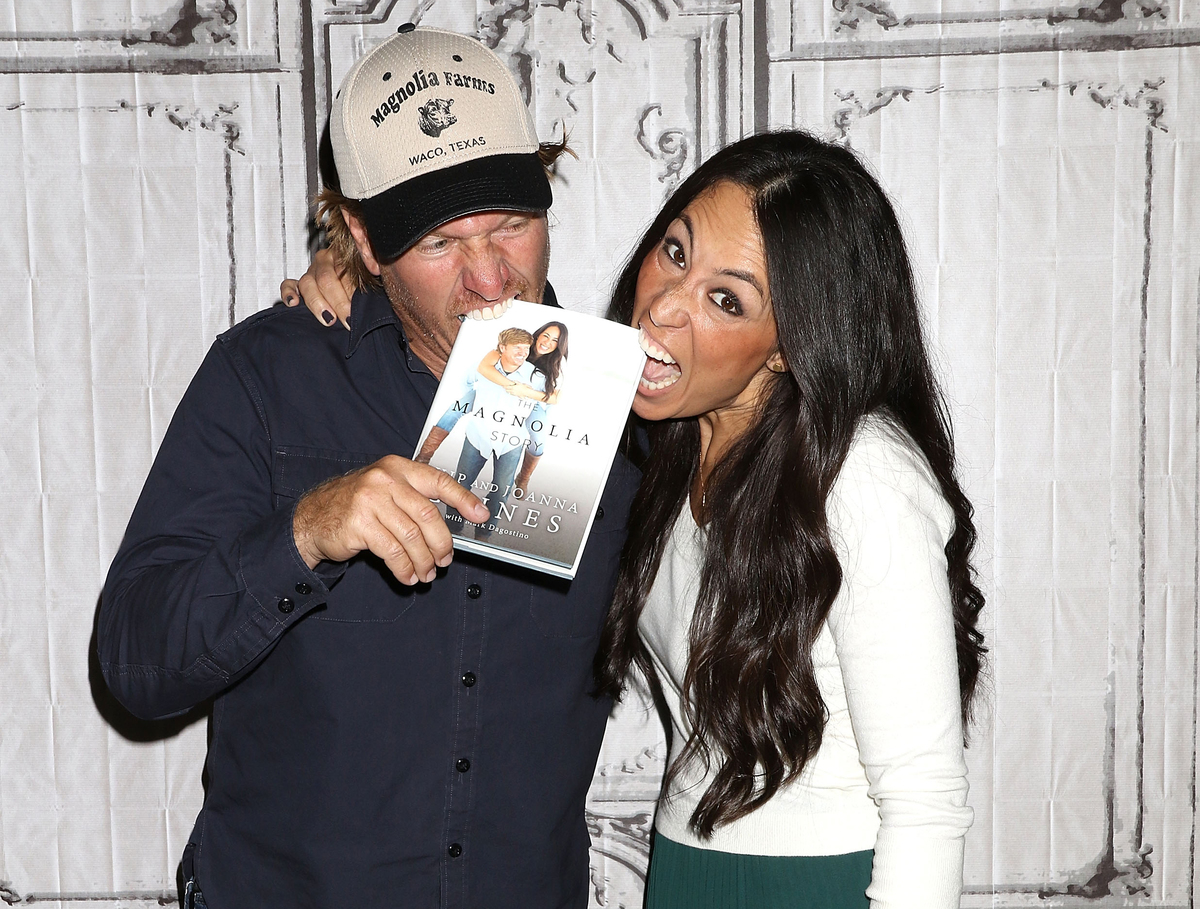 Chip and Joanna Gaines playfully bit at their book,