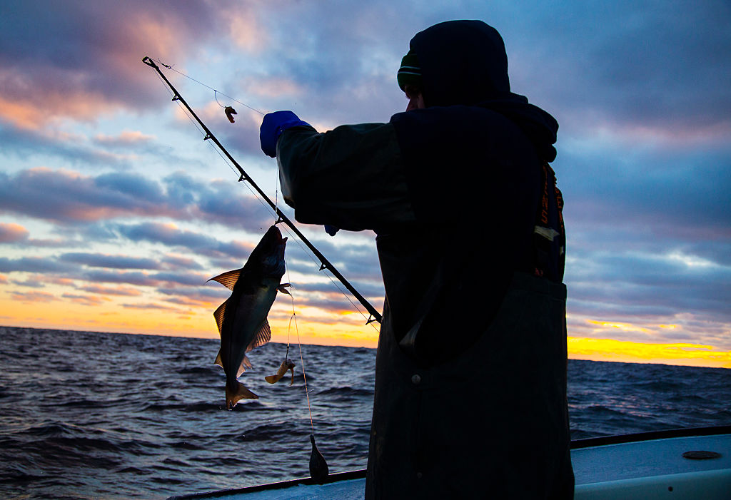 A silhouette of a man catching a fish is photographed at sunset.