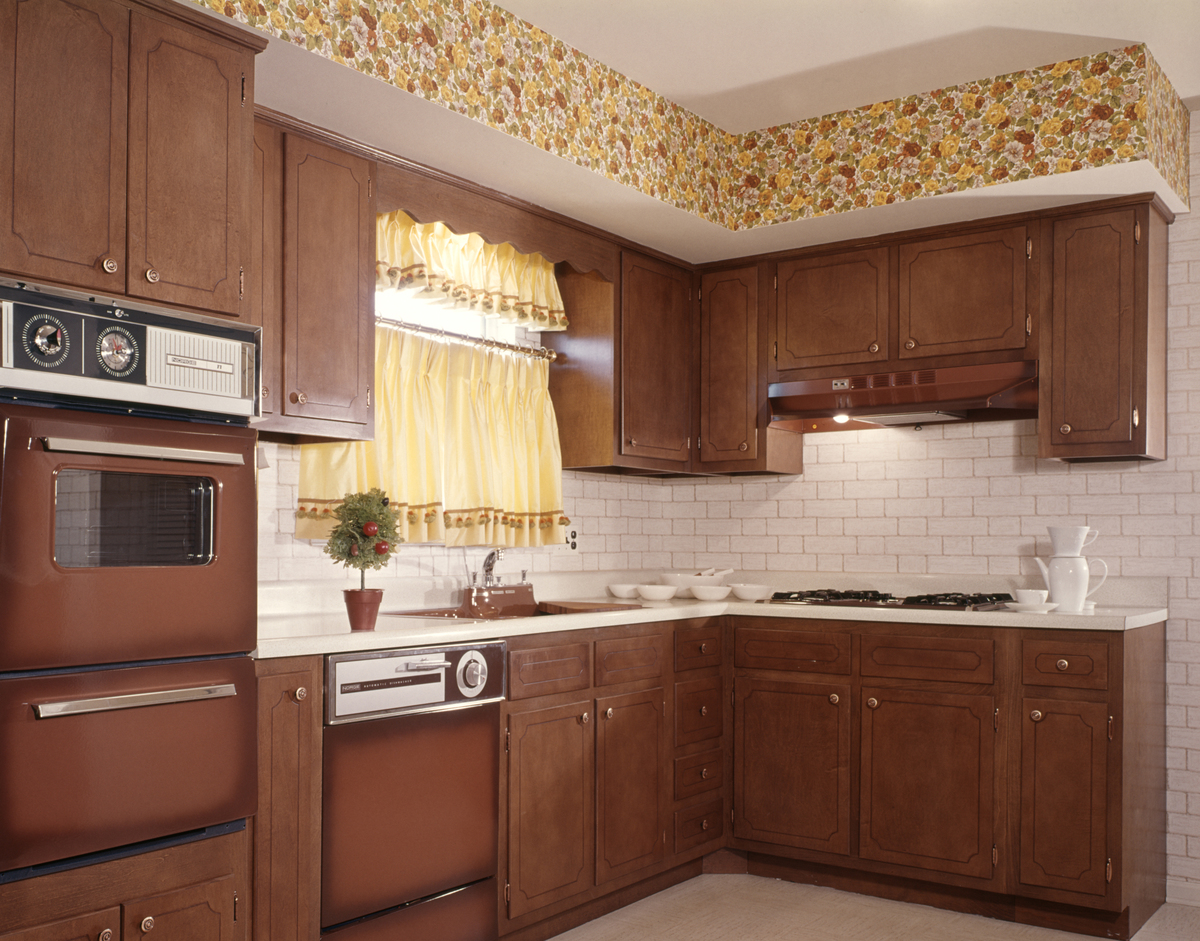 A 1970s kitchen features a yellow wallpaper border next to the ceiling.
