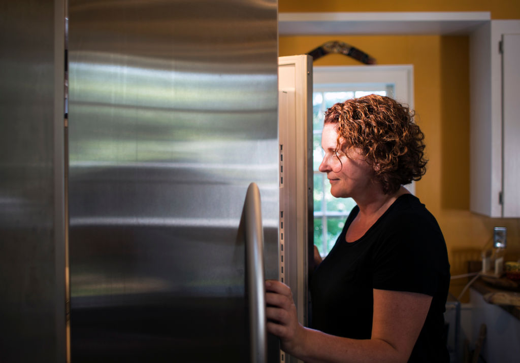 A woman looks into the fridge.