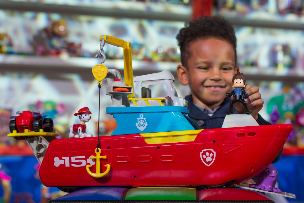 A boy plays with a Paw Patrol toy set.