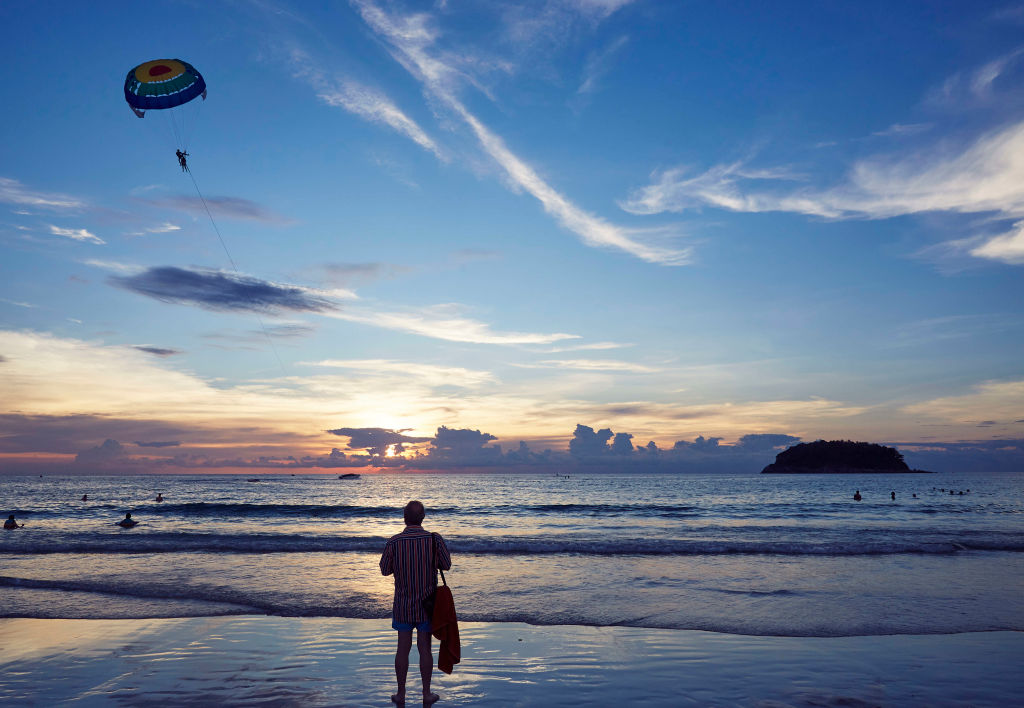A man stands alone on a beach during sunset.