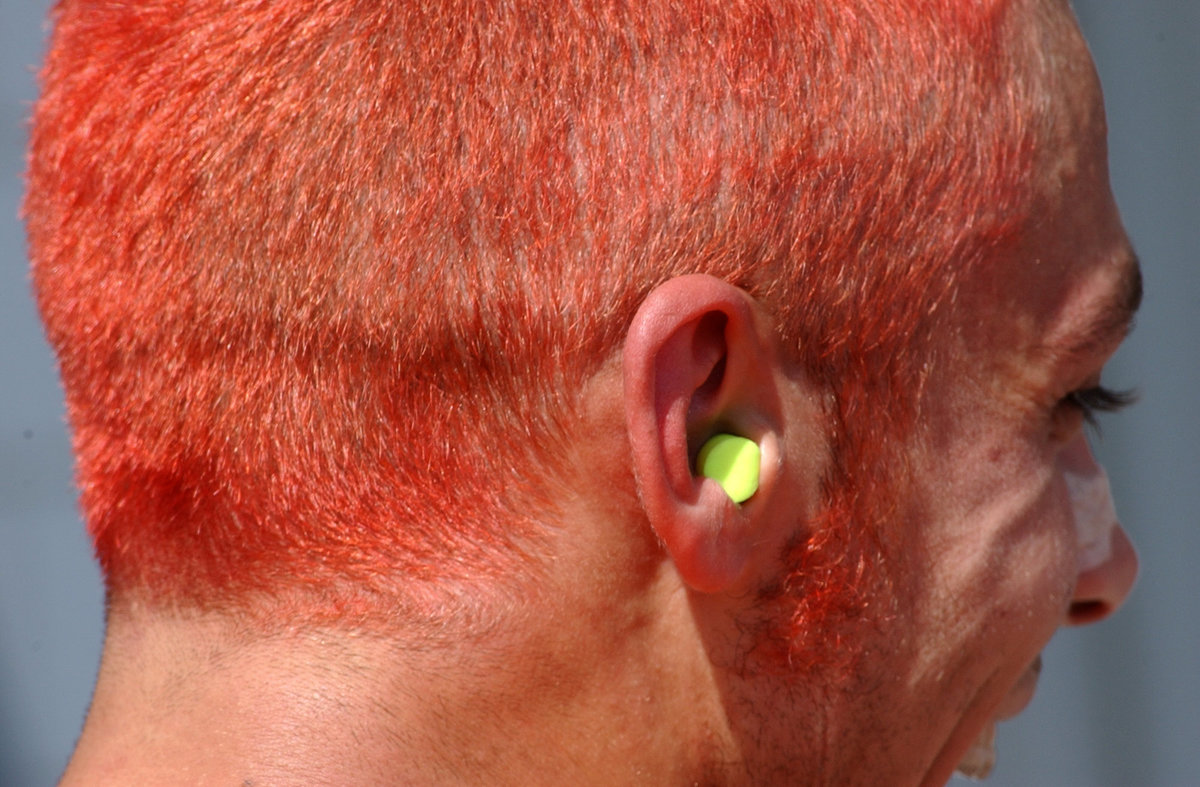 The orange head of 'The Doctor' Valentino Rossi has an ear plug in his ear.