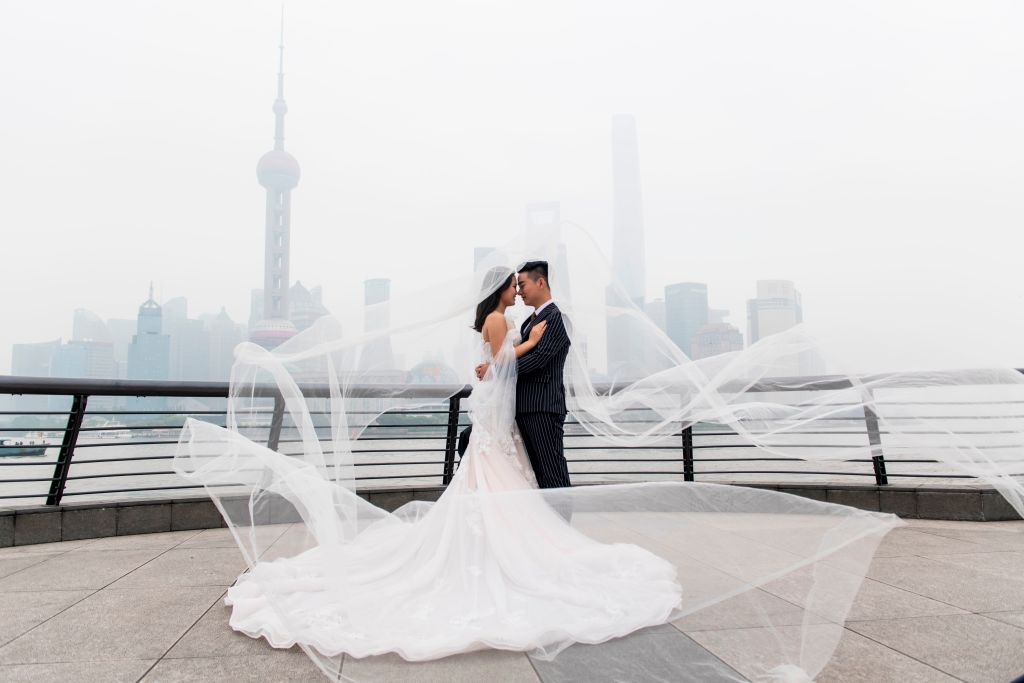 A couple poses for photos on their wedding day.