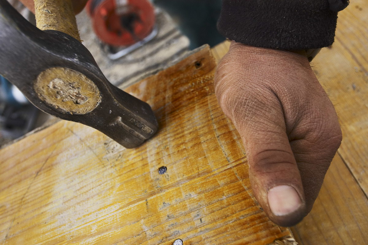 A carpenter hammers nails into a plank of wood.