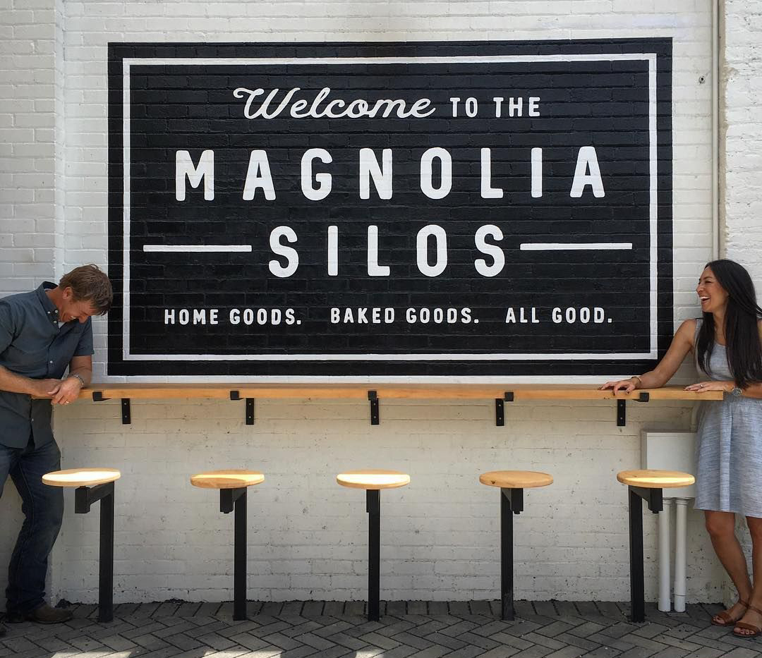 Joanna and Chip Gaines stand on the sides of the sign for Magnolia Silos.
